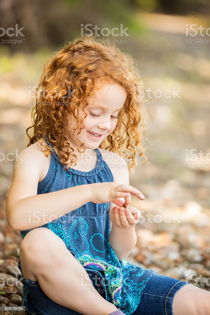 Girl With Curly Red Hair Playing On Riverbank stock photo