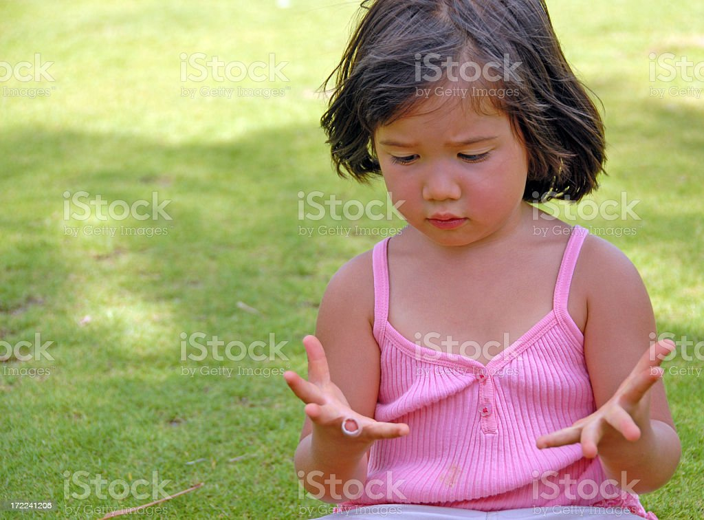 Girl with dark hair counting fingers on the grass royalty-free stock photo