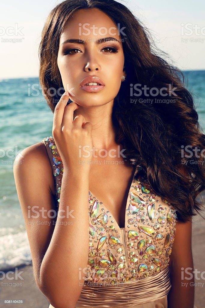 girl with dark hair in luxurious dress posing on beach stock photo
