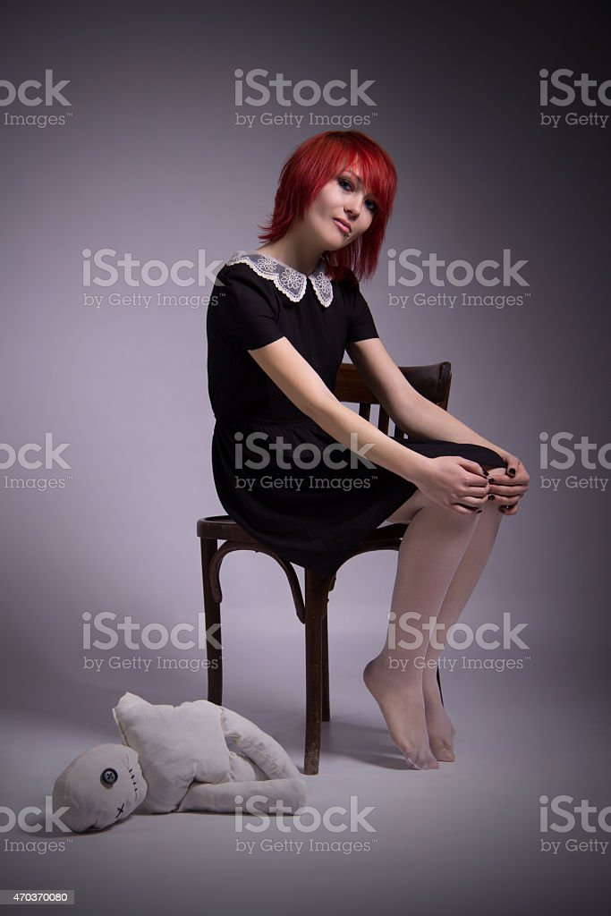 Girl with doll in a gloomy atmosphere stock photo