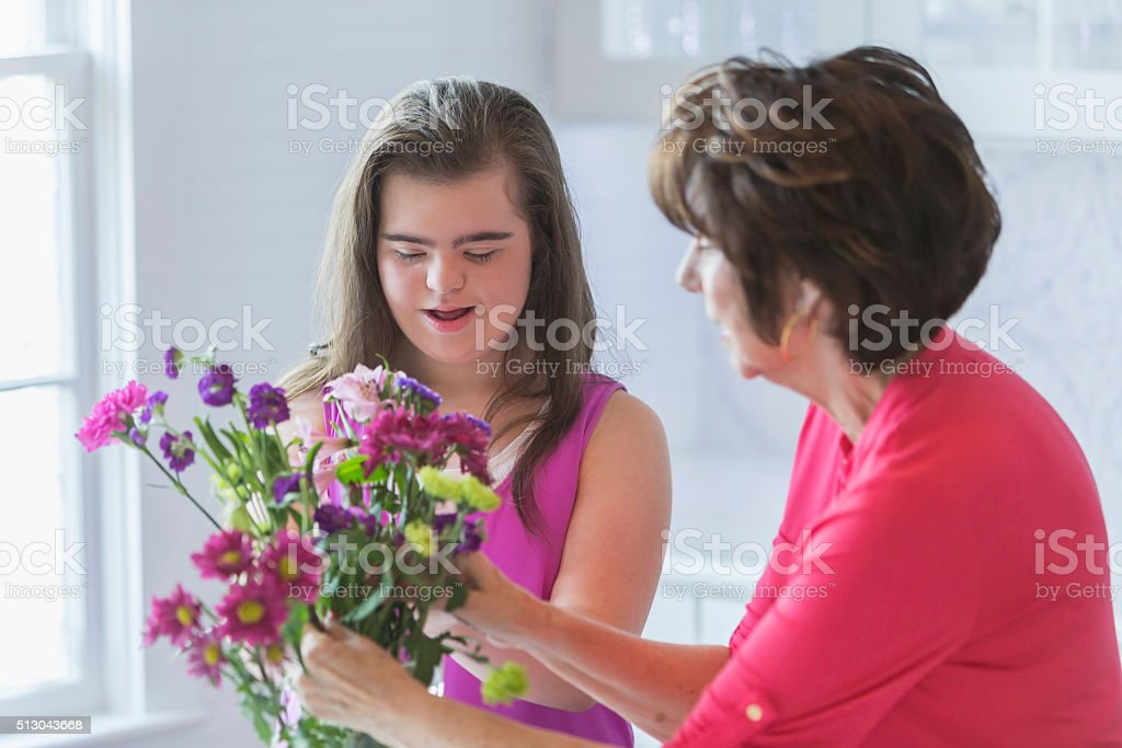 Girl with down syndrome, grandmother arranging flowers stock photo