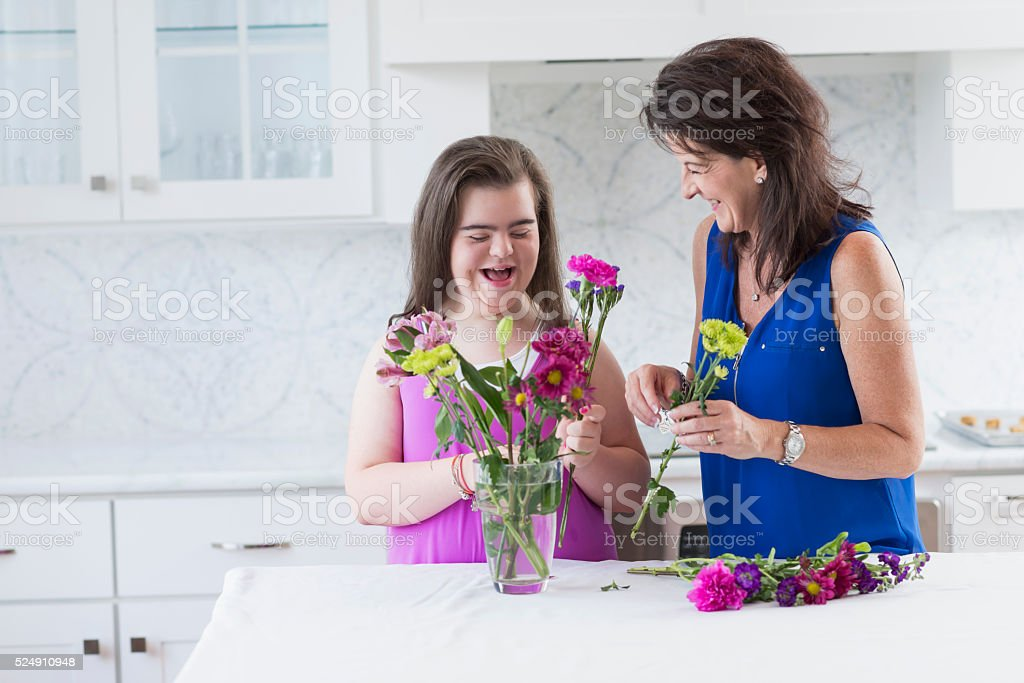 Girl with down syndrome, mother arranging flowers stock photo