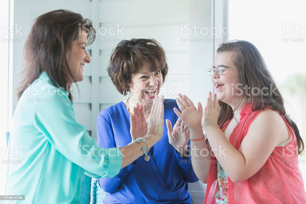 Girl with downs syndrome, mother, grandmother playing stock photo