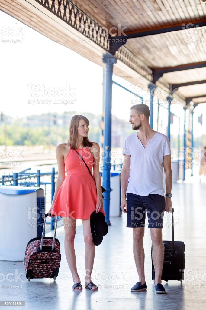 Girl with earnes, smileless expression and man with smily on his face, caucasian couple wearing summer casual dress walking with the suitcases through the train station. Photo taken at summer daytime. stock photo