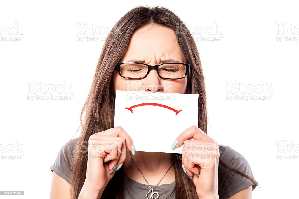 Girl with eyes closed and sad smile drawn on paper stock photo
