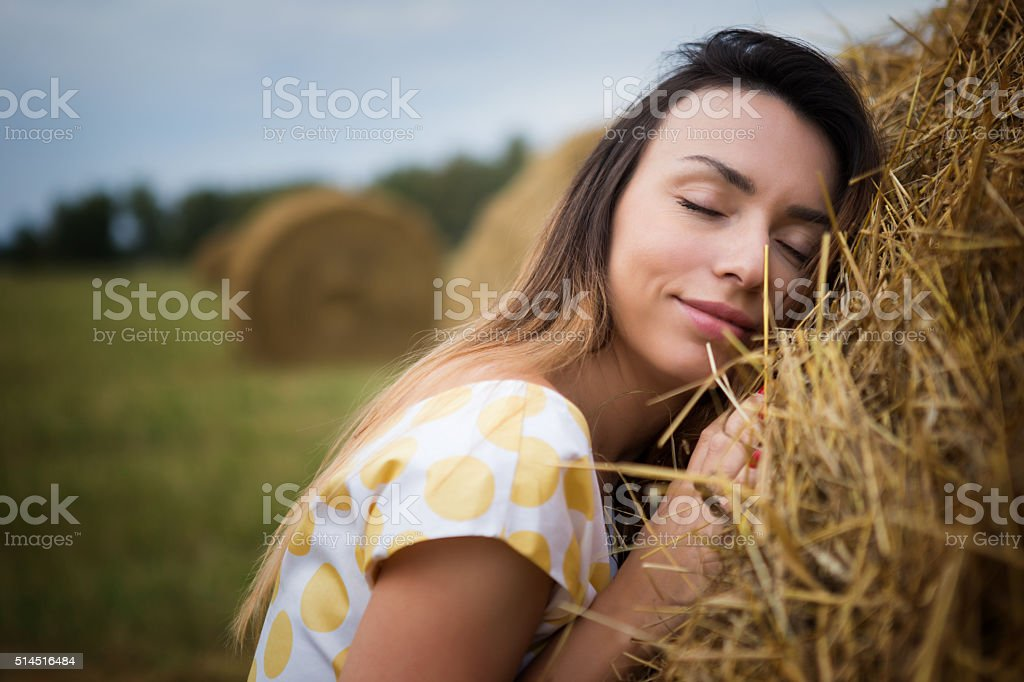 girl with eyes closed leaning against the hayloft stock photo