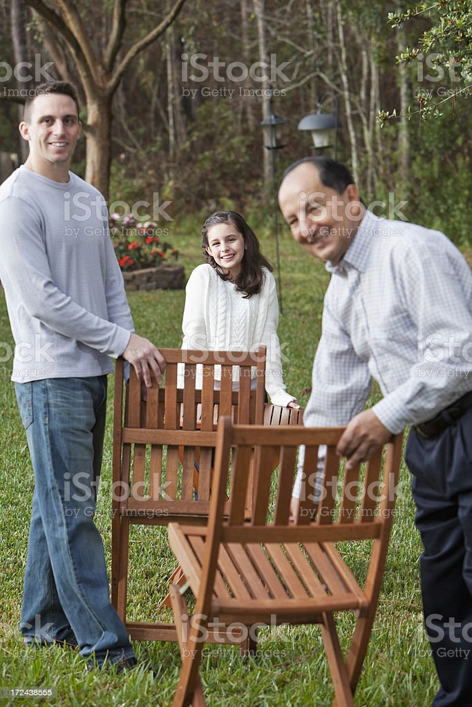 Girl with father and grandfather setting up chairs stock photo