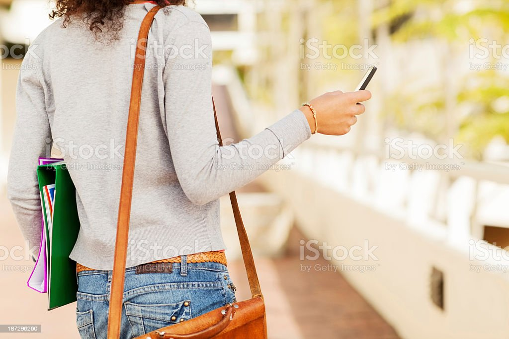 Girl With Files And Bag Using Smart Phone On Campus stock photo