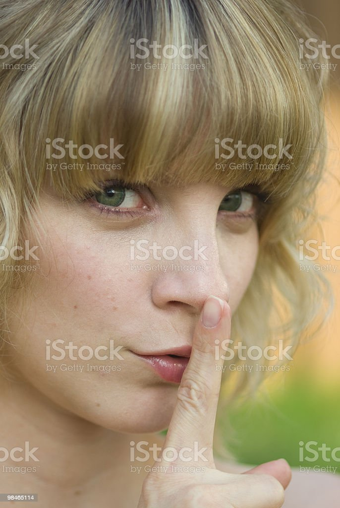 Girl with finger on lips stock photo