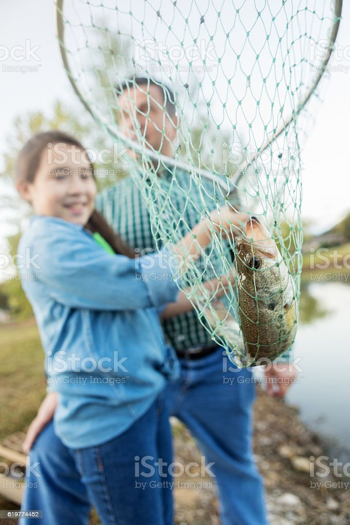 Girl with fish in a fishing net stock photo