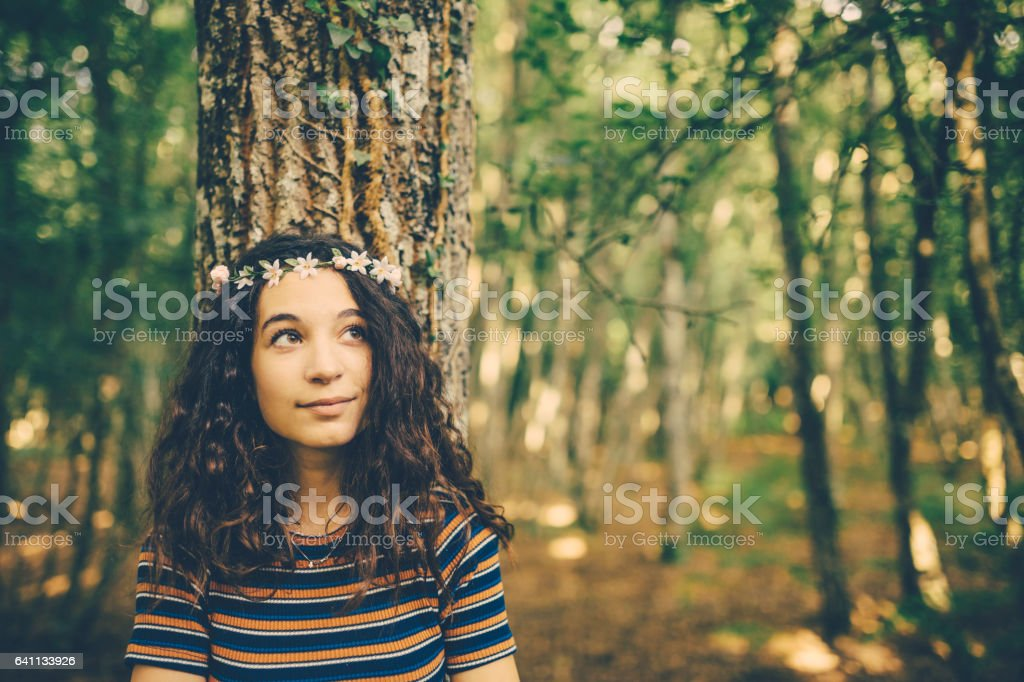 Girl with floral crown enjoying nature in the forest stock photo