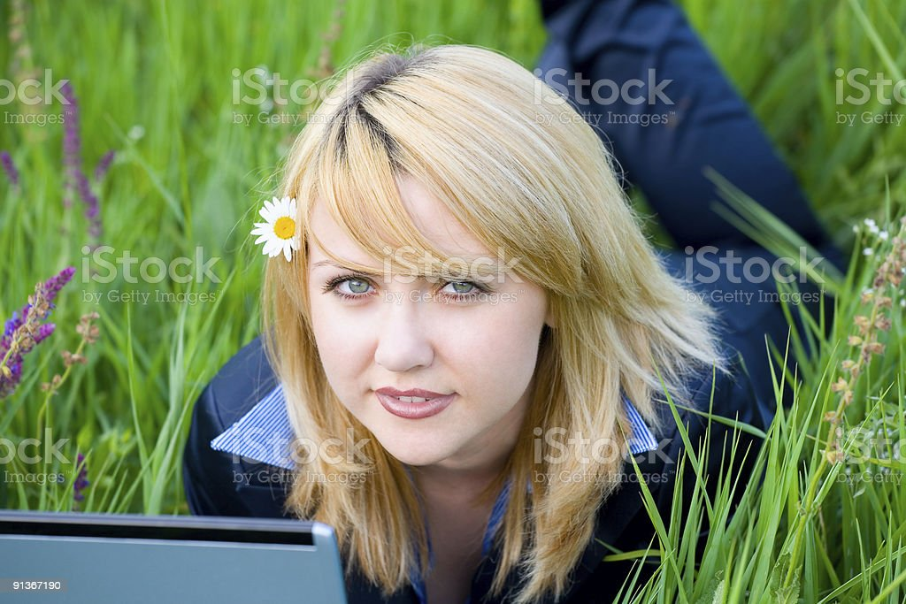 Girl with flower in hair lying on grass #1 royalty-free stock photo