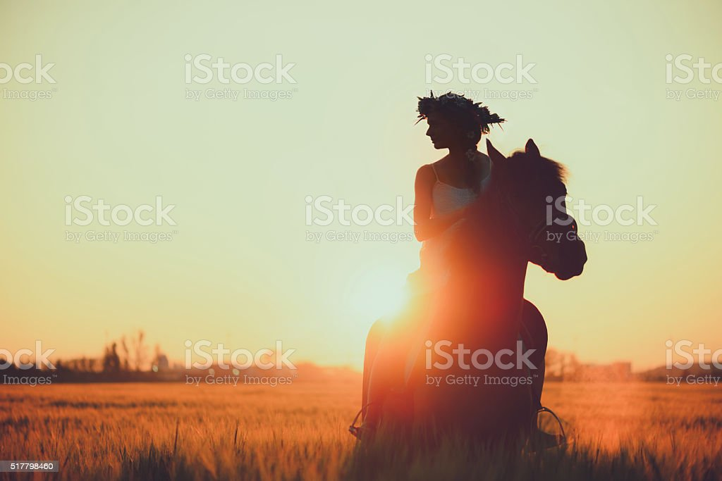 Girl with flowers wreathwhile riding horse at sunset stock photo