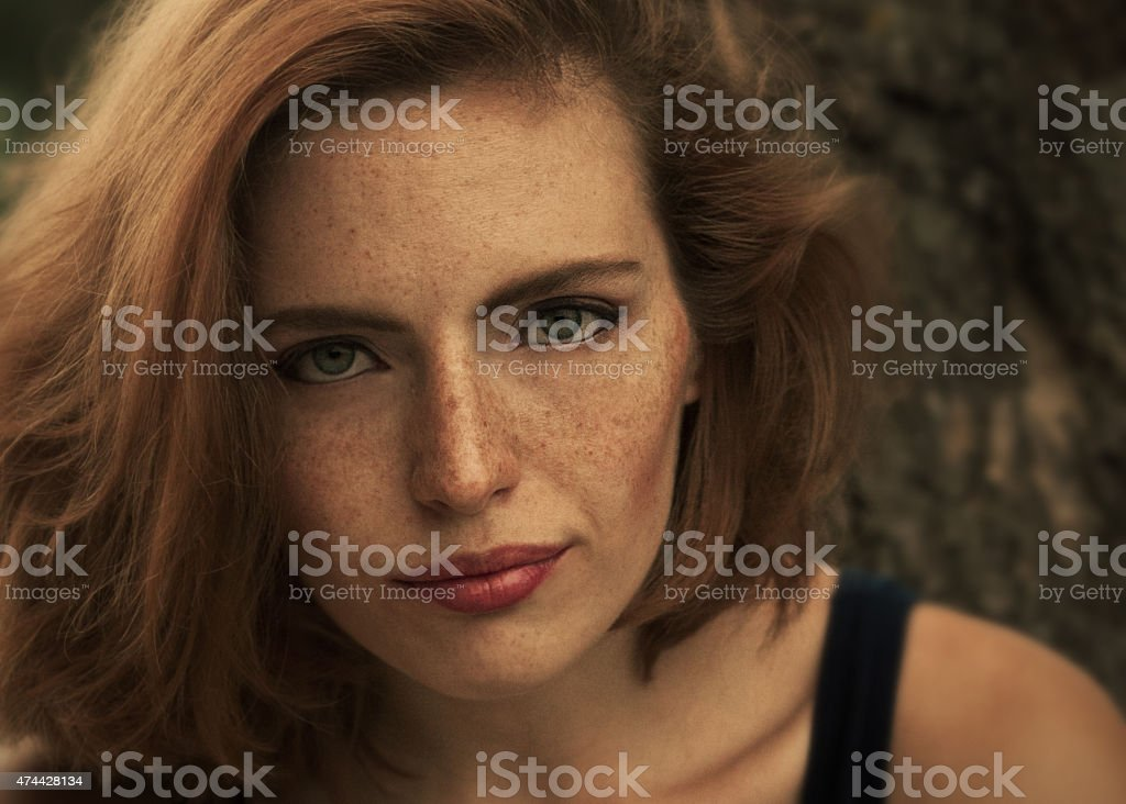 girl with freckles in brown tones stock photo