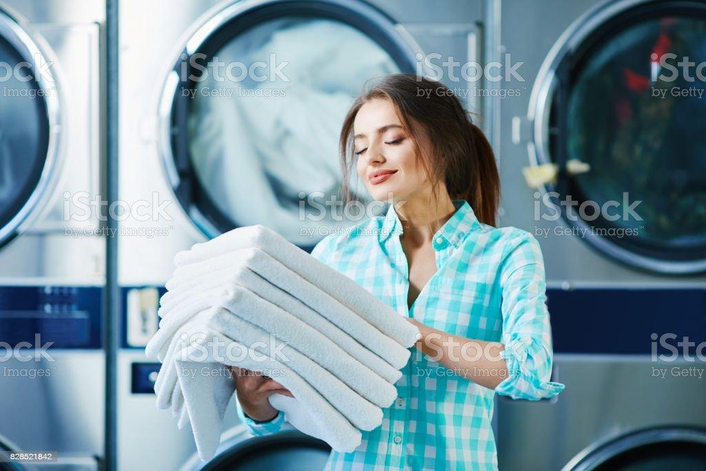 Girl with fresh soft  linen near washing machines stock photo