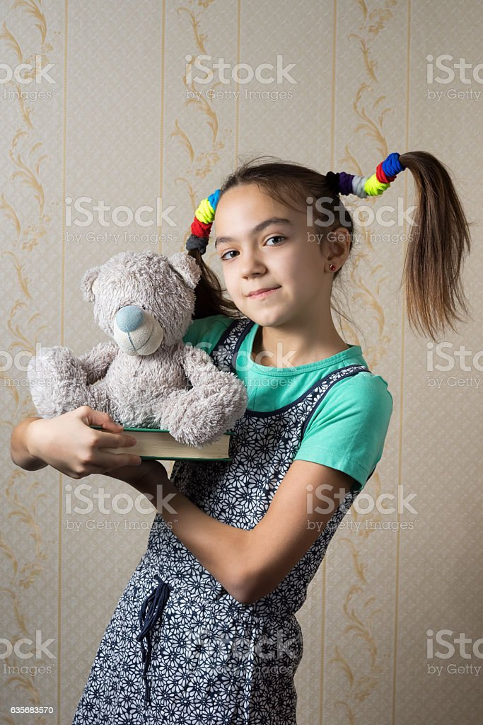 girl with funny tails is holding a teddy bear stock photo