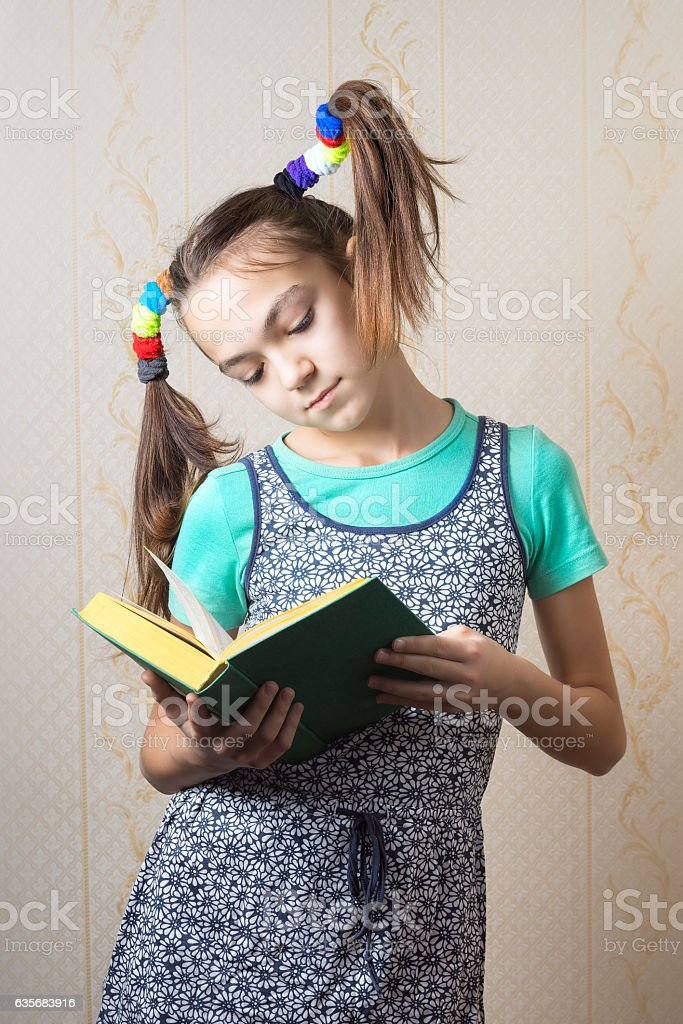 girl with funny tails is reading a book. stock photo
