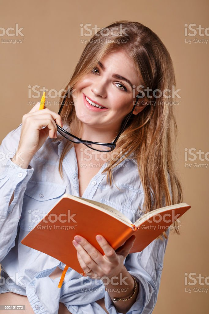 Girl with glasses holds a notebook and pen. stock photo