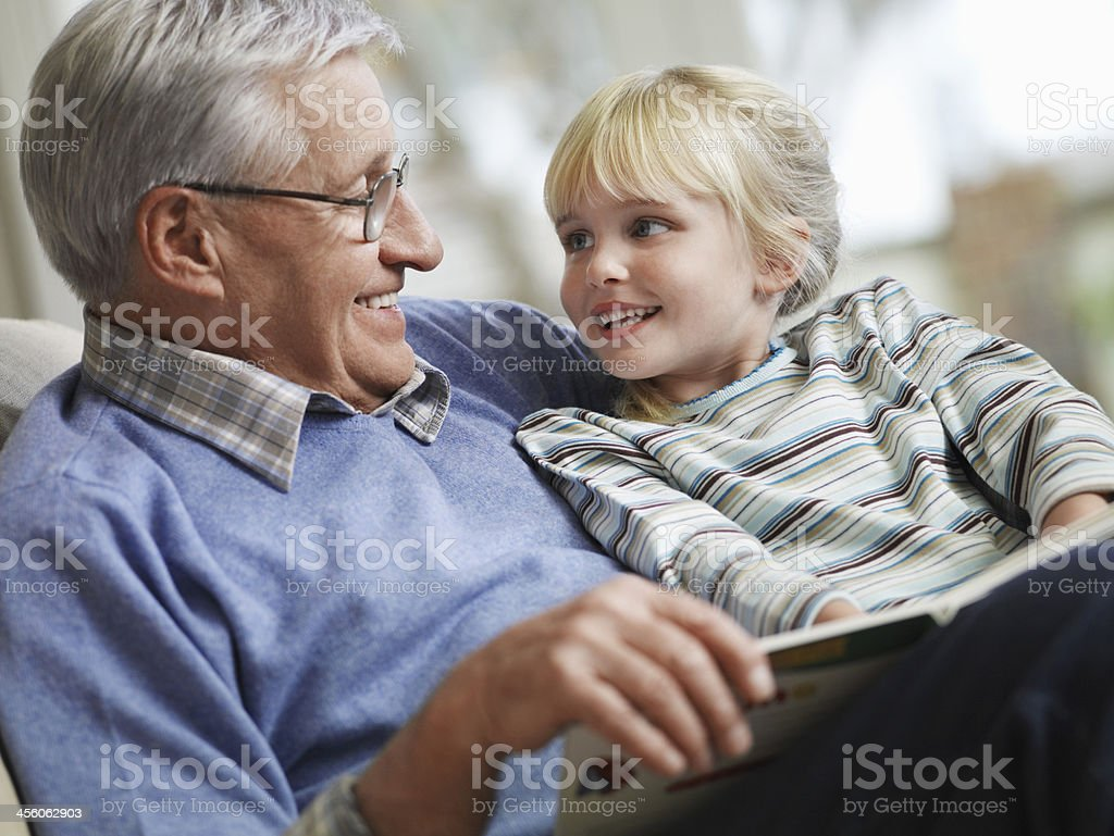 Girl With Grandfather Reading Story Book stock photo