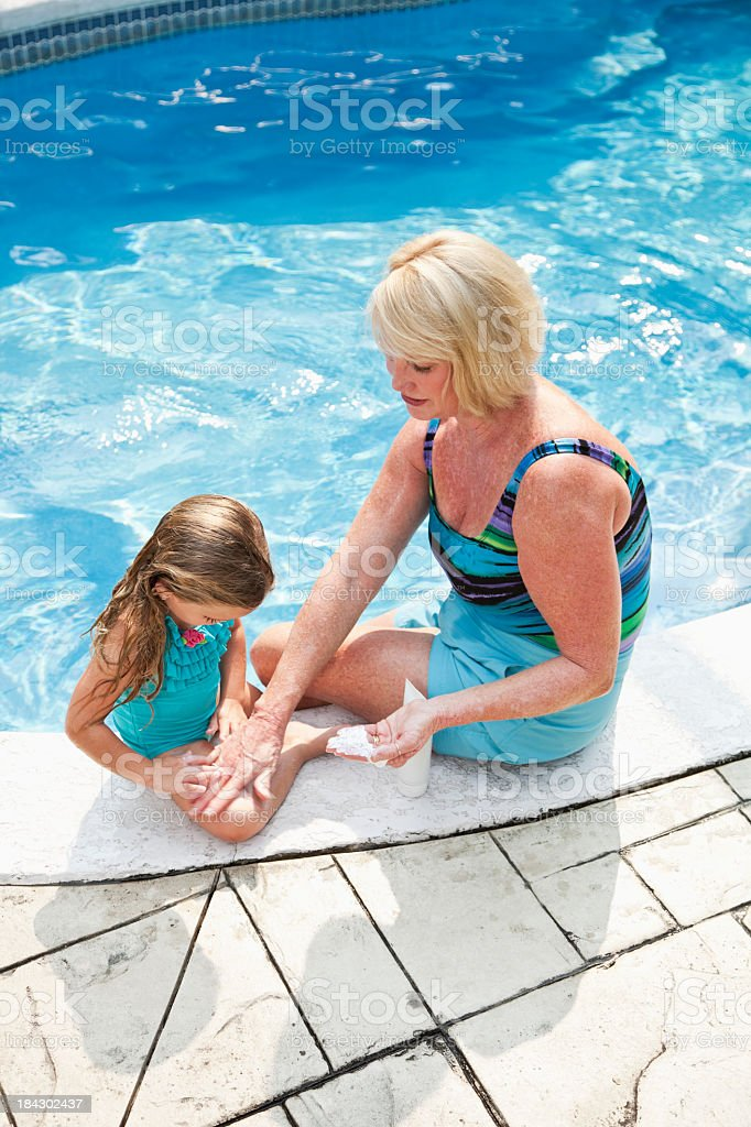 Girl with grandma putting on sunscreen royalty-free stock photo