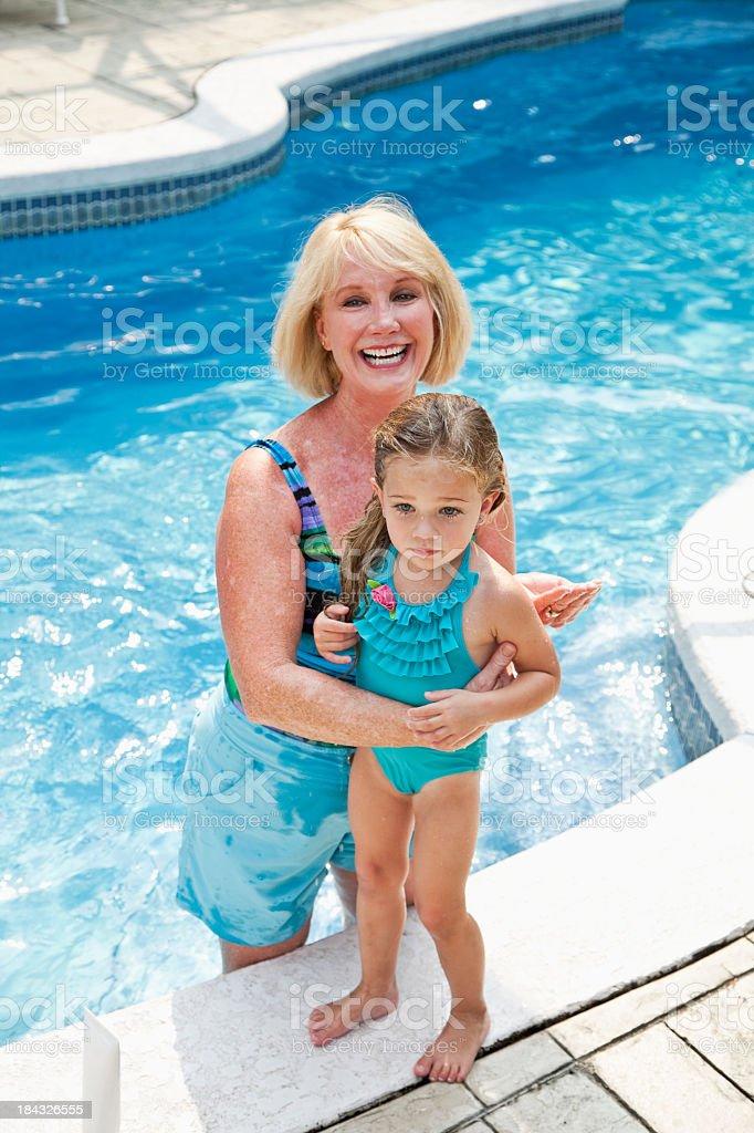 Girl with grandma putting on sunscreen stock photo