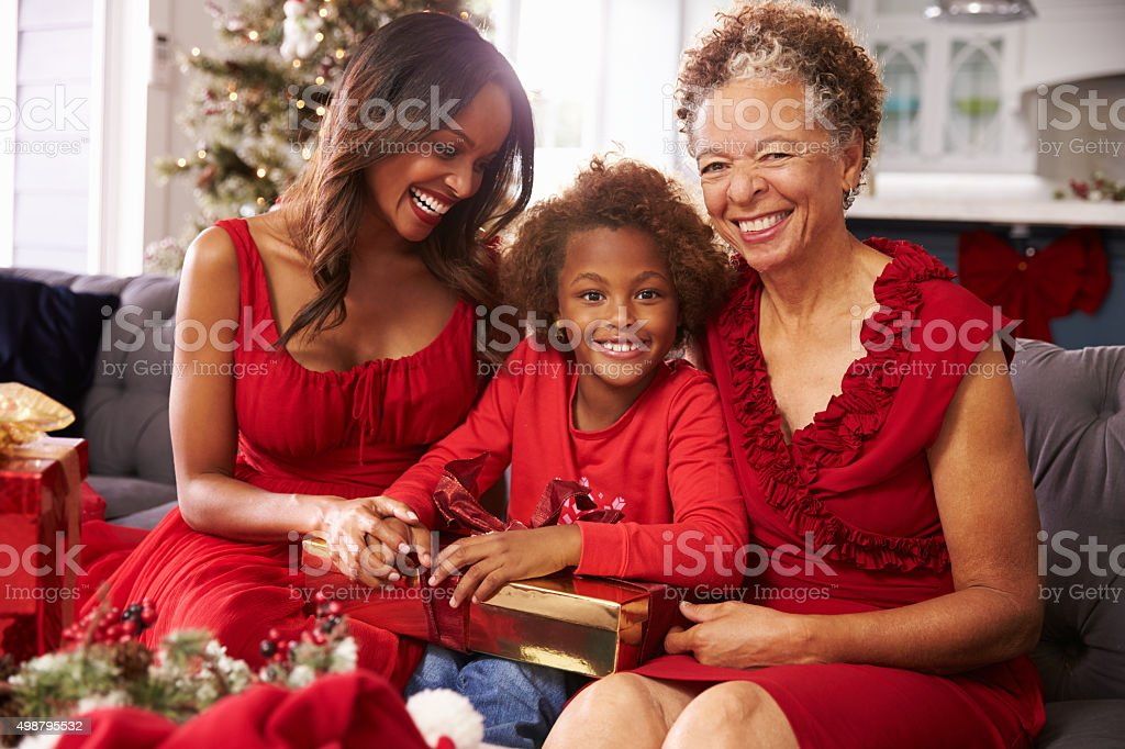 Girl With Grandmother And Mother Opening Christmas Gifts stock photo