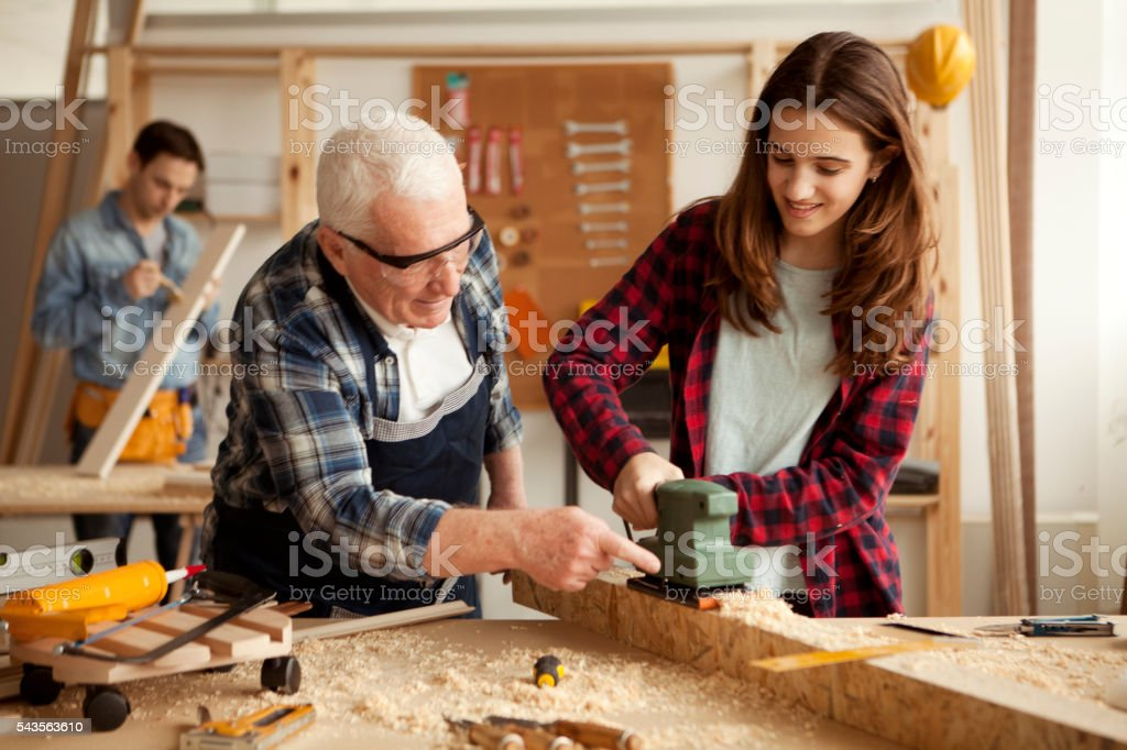 Girl with grandpa and father at woodshop stock photo