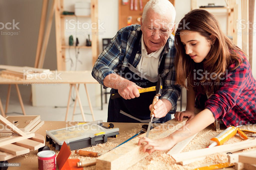Girl with grandpa at workshop stock photo
