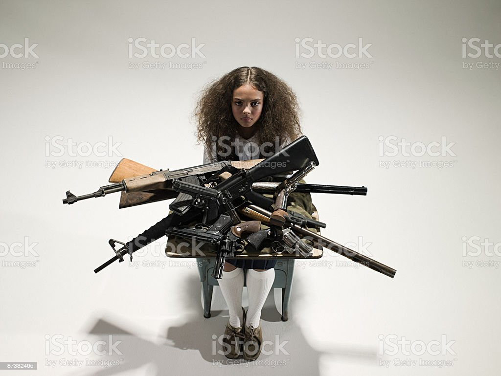 Girl with guns on her desk royalty-free stock photo