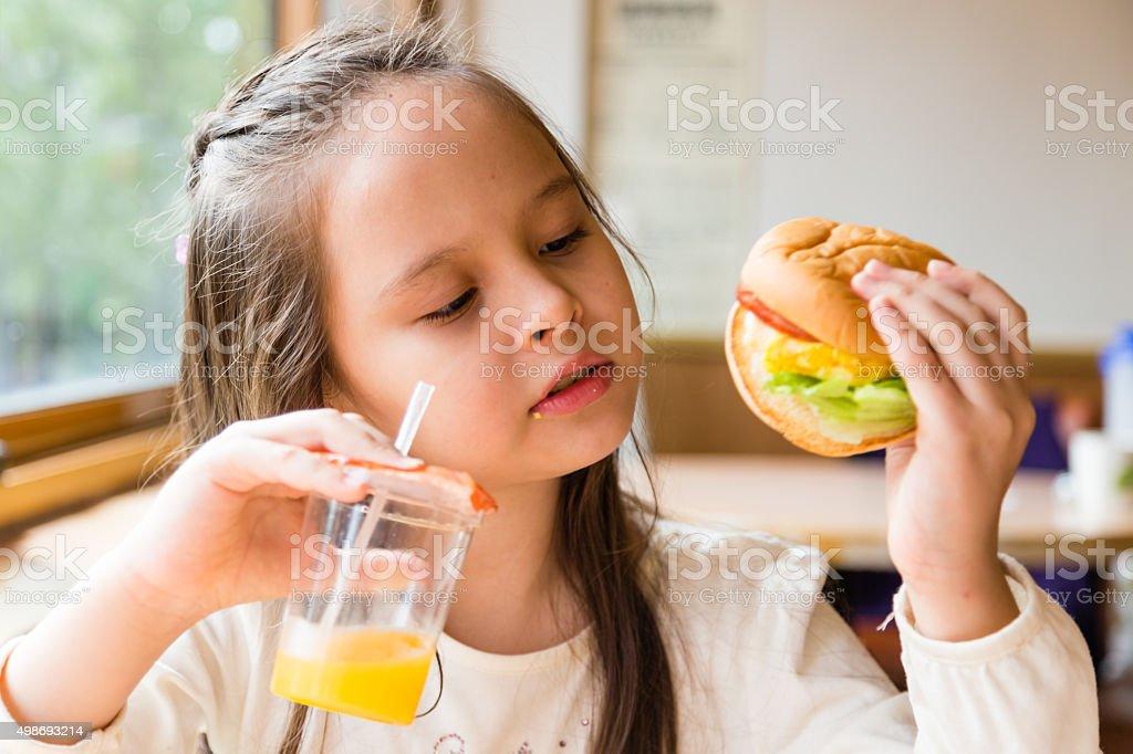 Girl with hamburger and orange juice stock photo