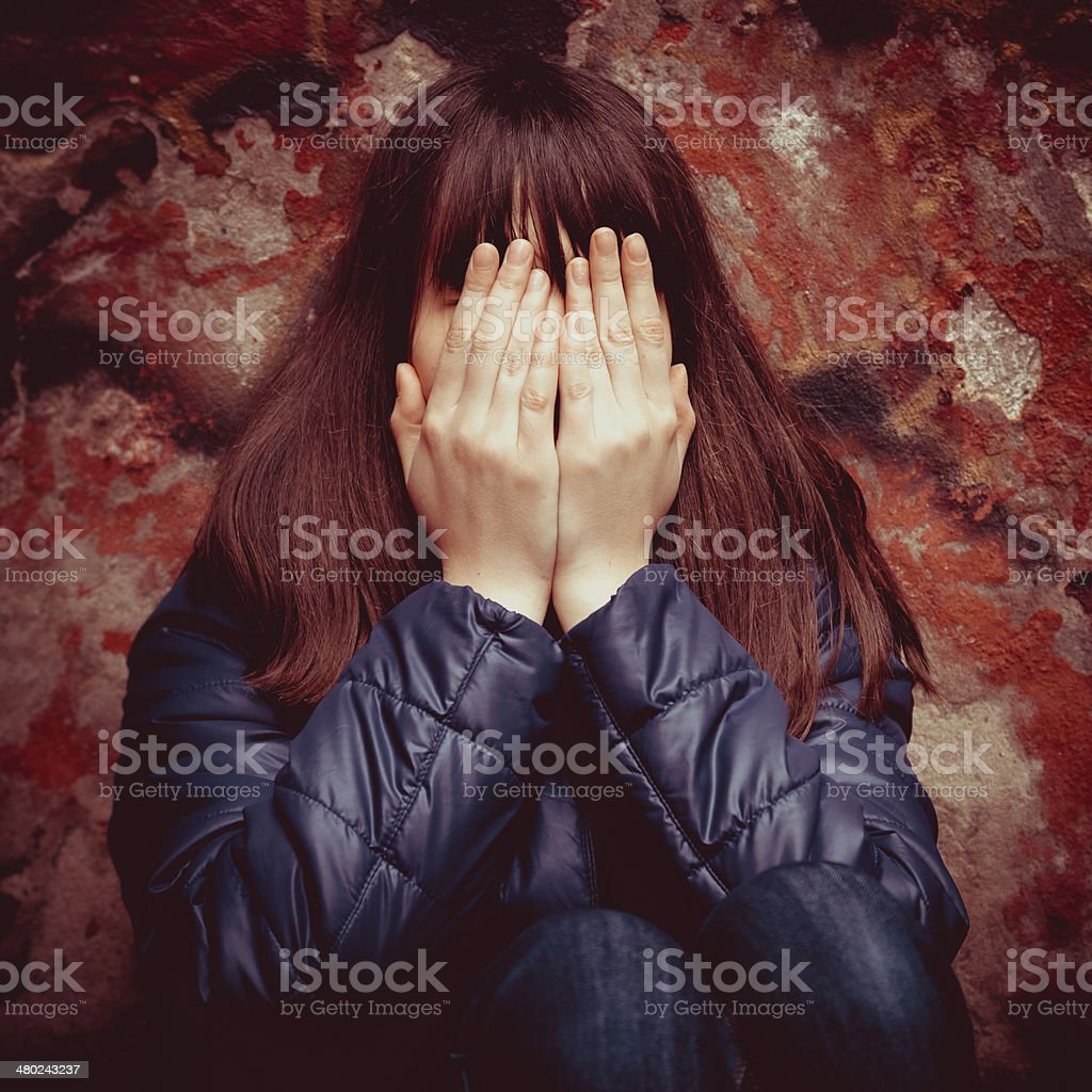 girl with hands over eyes near wall outdoors stock photo