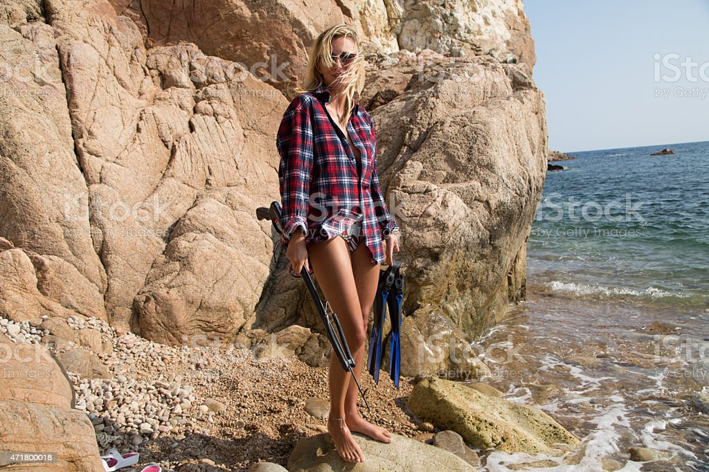 Girl with harpoon in flannel shirt on the rocky beach stock photo