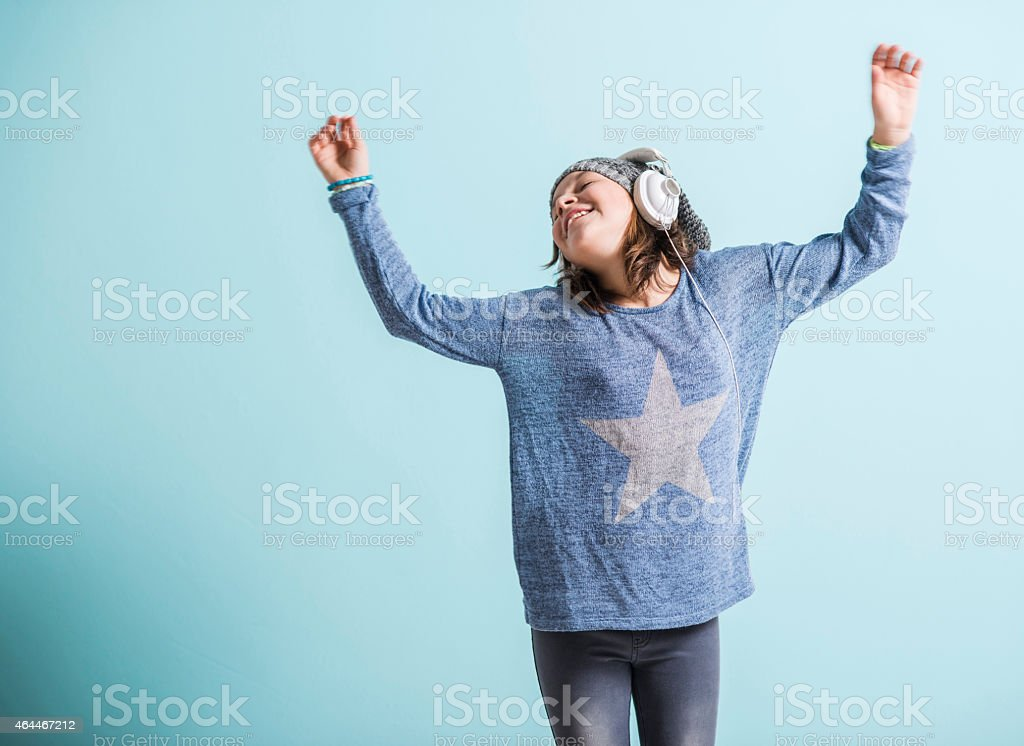 Girl with head phones dancing and listening to music stock photo