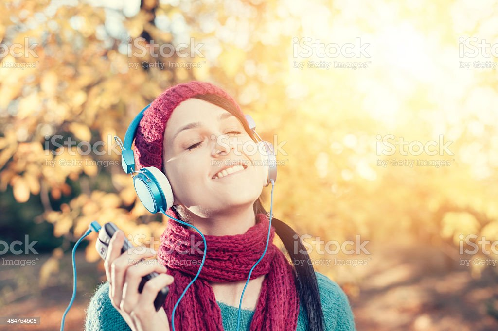 Girl with headphones enjoying the music in the park stock photo