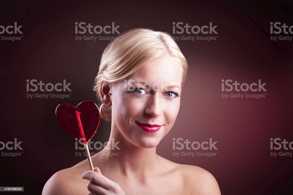 Girl with heart lollipop on black background royalty-free stock photo