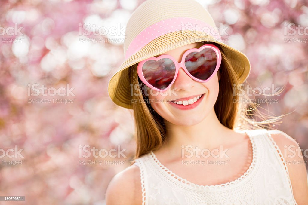 Girl with heart shape sunglasses in spring park royalty-free stock photo
