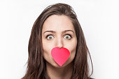 Girl with heart-shaped post-it on her mouth