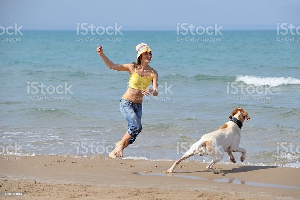 girl with her dog on the beach royalty-free stock photo