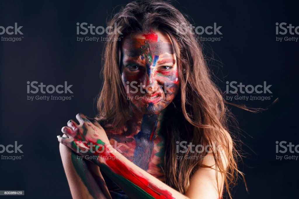 Girl with her face painted with her own hands. stock photo