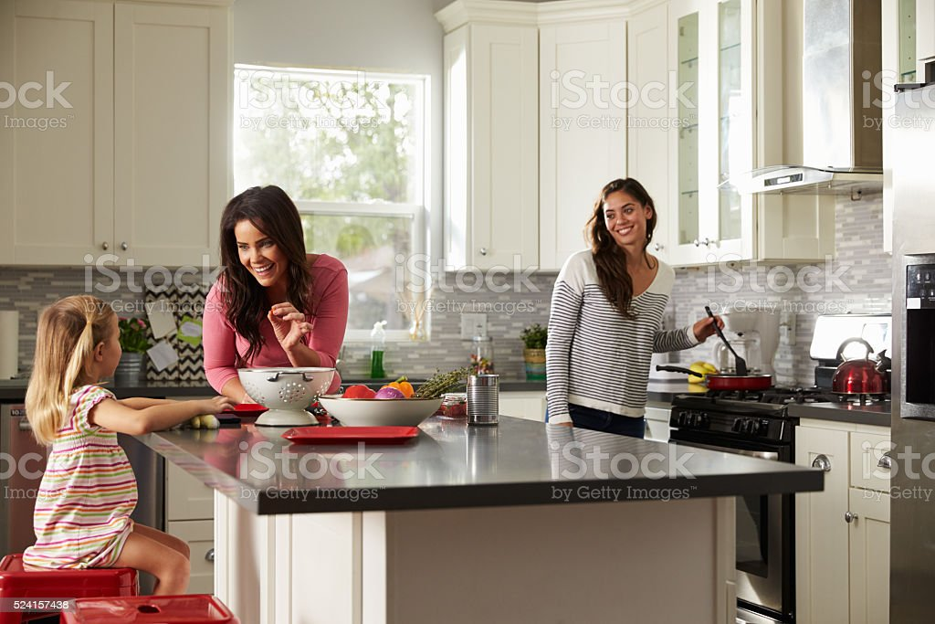 Girl with her female parents, preparing meal in the kitchen stock photo