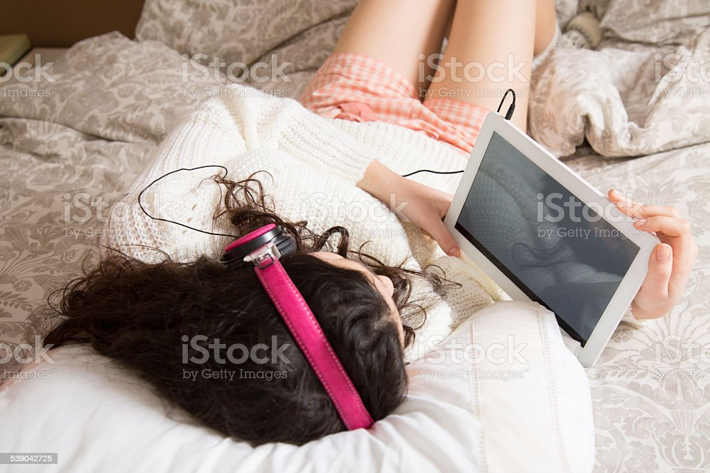 Girl with her tablet in bed stock photo