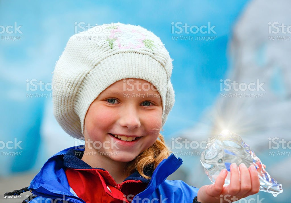 Girl with ice piece near Nigardsbreen glacier (Norway) stock photo