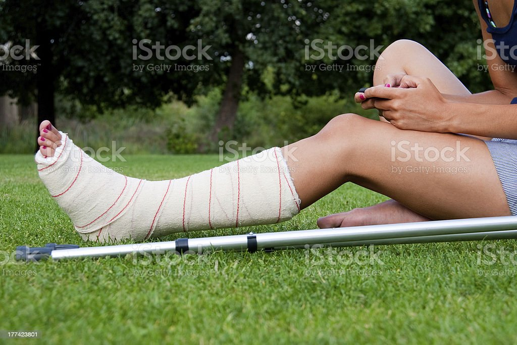 Girl with leg in plaster using her smartphone stock photo