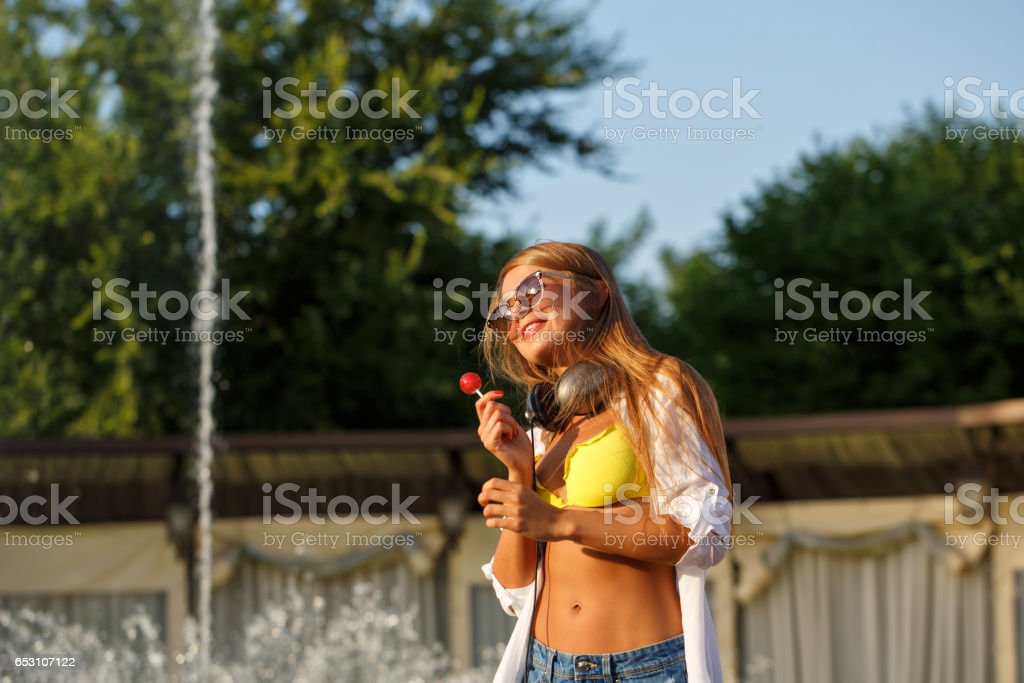 Girl with lollipop and headphone stock photo