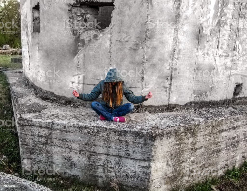 A girl with long blond hair in a hood sits in a lotus pose stock photo