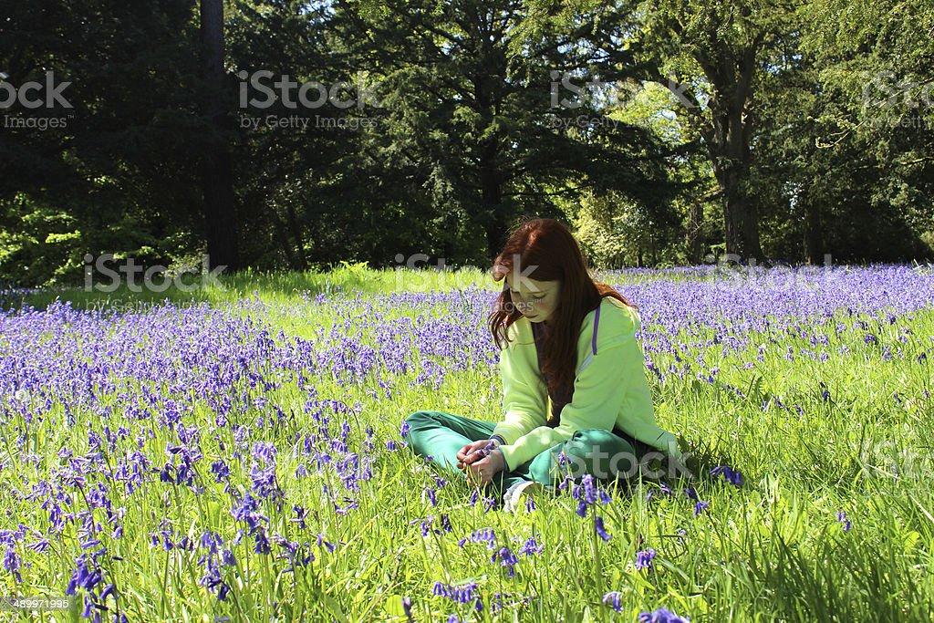 Girl with long hair sitting amongst woodland bluebells, dappled shade royalty-free stock photo