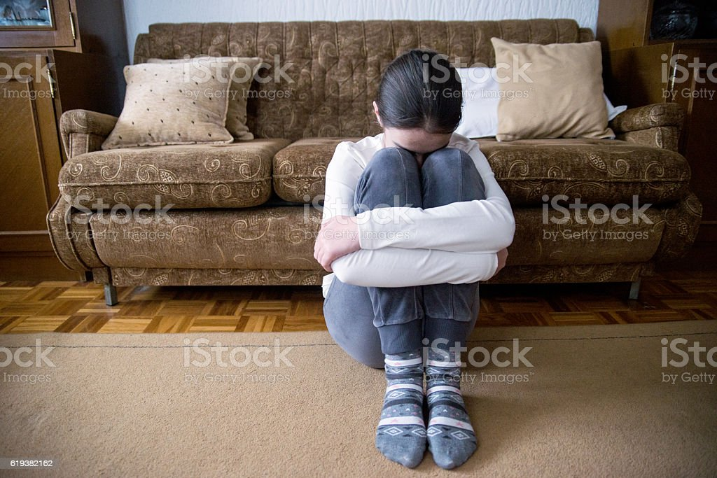girl with lower head on her knee sitting beside bed stock photo