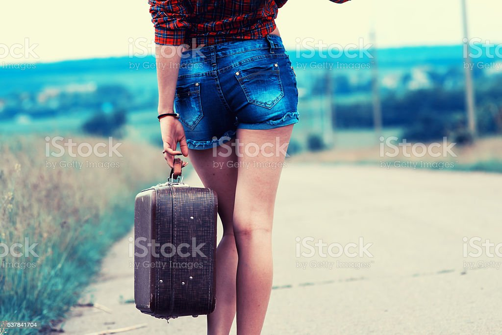 girl with luggage on the road stock photo