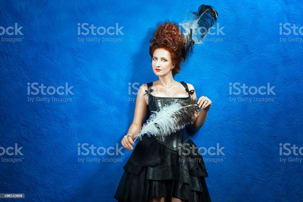 Girl with lush hair high in a corset and skirt. stock photo