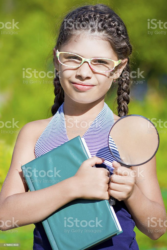 Girl with magnifying glass and book royalty-free stock photo